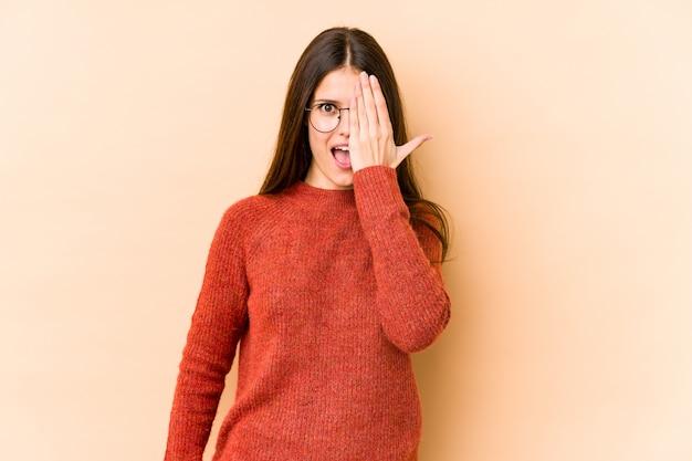 Jeune femme caucasienne sur mur beige s'amuser couvrant la moitié du visage avec la paume.