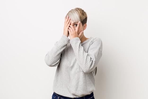Jeune femme caucasienne sur le mur blanc cligner des yeux effrayé et nerveux.