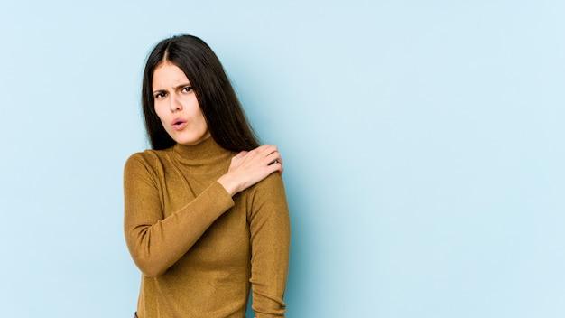 Jeune femme caucasienne sur mur bleu ayant une douleur à l'épaule.