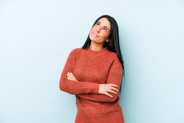 Jeune femme caucasienne sur un mur bleu fatigué d'une tâche répétitive.