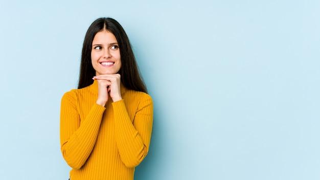 Jeune femme caucasienne sur mur bleu garde les mains sous le menton, regarde joyeusement de côté.