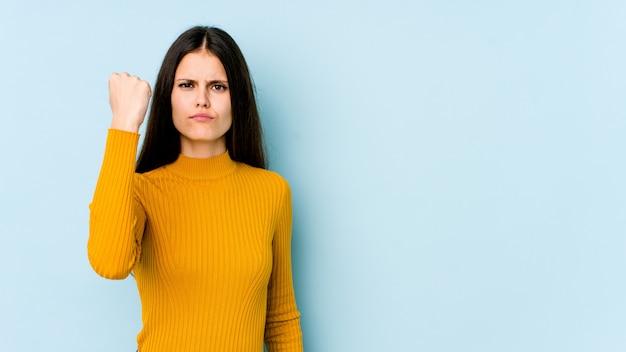 Jeune femme caucasienne sur mur bleu montrant avec une expression faciale agressive.