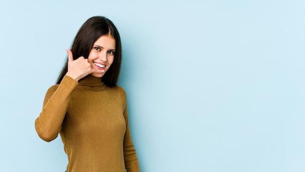 Jeune femme caucasienne sur mur bleu montrant un geste d'appel de téléphone mobile avec les doigts.