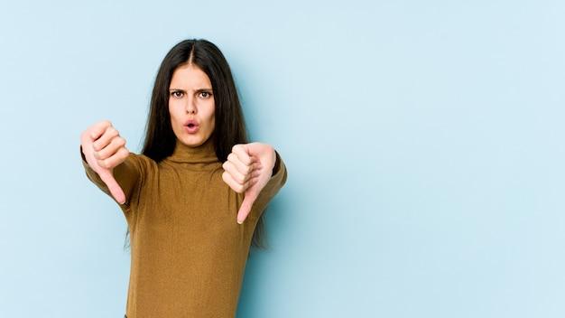 Jeune femme caucasienne sur mur bleu montrant le pouce vers le bas et exprimant l'aversion.