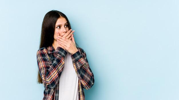Jeune femme caucasienne sur mur bleu réfléchie à la recherche d'un espace vide couvrant la bouche avec la main.