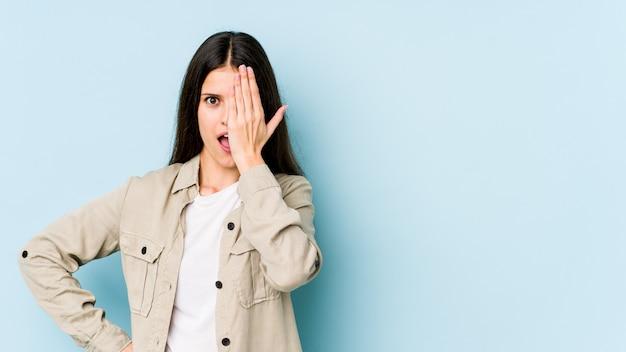 Jeune femme caucasienne sur mur bleu s'amuser couvrant la moitié du visage avec la paume.