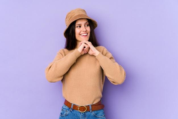 Jeune femme caucasienne sur mur violet garde les mains sous le menton, regardant joyeusement de côté.