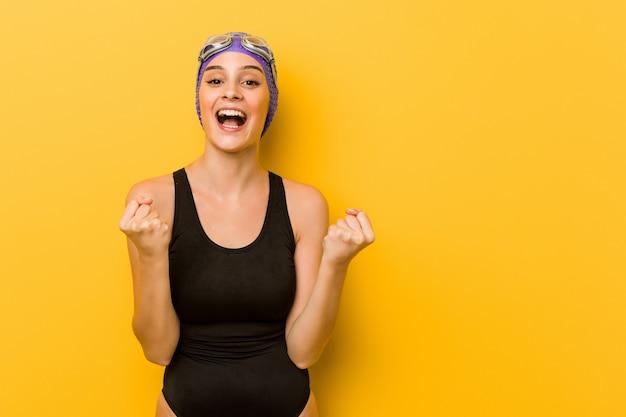 Jeune femme caucasienne de nageur acclamant insouciant et excité. la victoire .