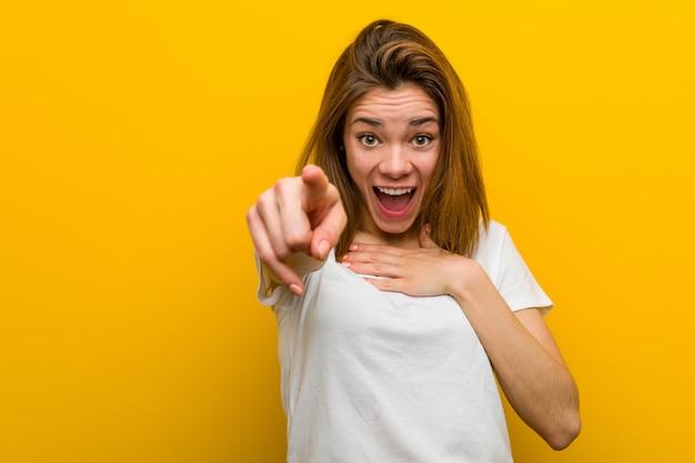 Jeune femme caucasienne naturelle pointe avec le pouce loin, rire et insouciant.