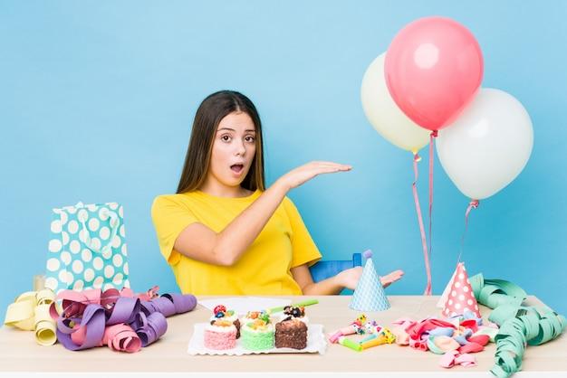 Jeune femme caucasienne organisant un anniversaire choqué et étonné tenant un espace de copie entre les mains.
