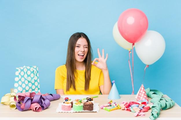 Jeune femme caucasienne organisant un anniversaire clignote un œil et détient un geste correct avec la main.