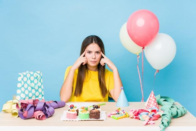 Jeune femme caucasienne organisant un anniversaire concentré sur une tâche, gardant les index pointant la tête.