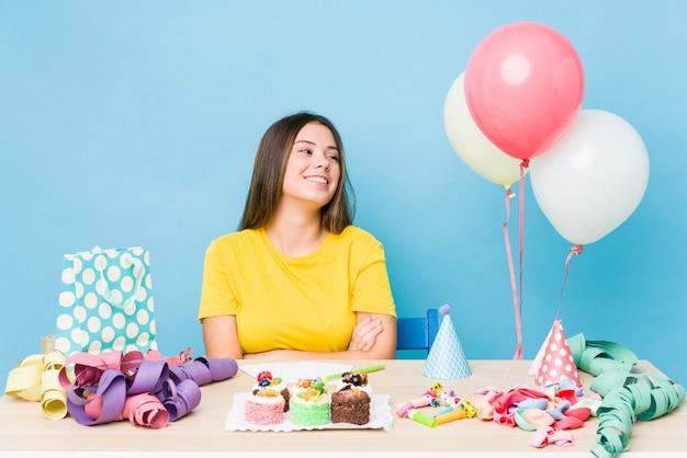 Jeune femme caucasienne organisant un anniversaire souriant confiant avec les bras croisés.