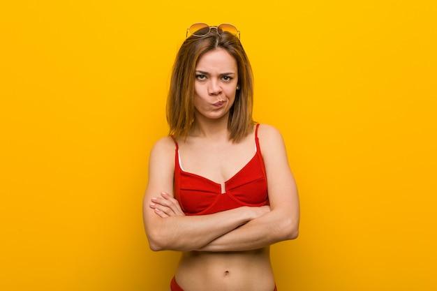 Jeune femme caucasienne portant bikini et lunettes de soleil malheureux à la recherche à huis clos avec une expression sarcastique.