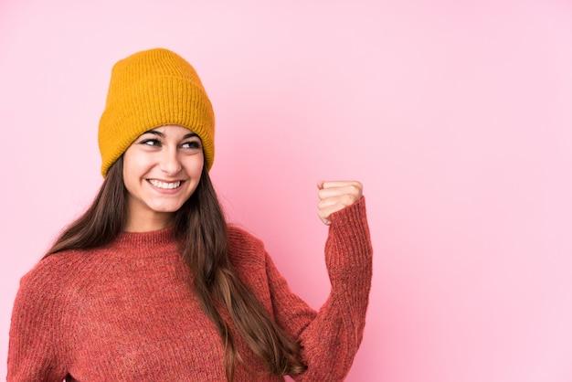 Jeune femme caucasienne portant un bonnet de laine levant le poing après une victoire, concept gagnant.