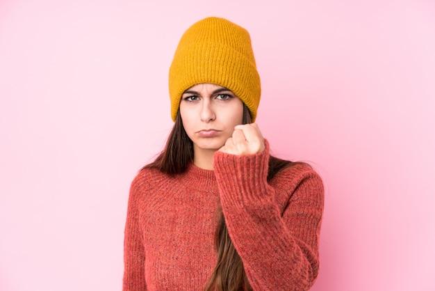 Jeune femme caucasienne portant un bonnet de laine montrant le poing avec une expression faciale agressive.