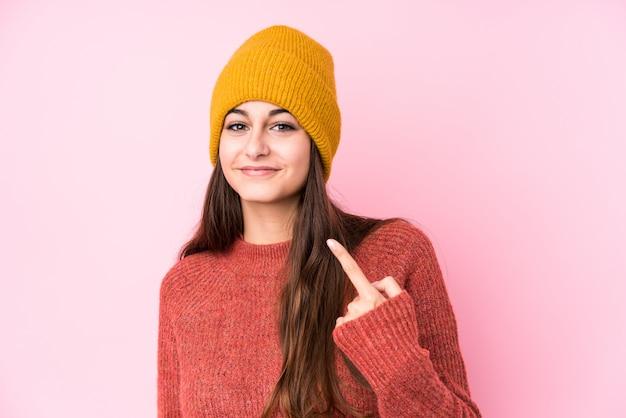 Jeune femme caucasienne portant un bonnet de laine pointant avec le doigt vers vous comme si vous vous invitiez à vous rapprocher.