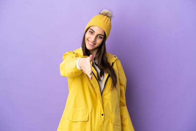 Jeune femme caucasienne portant un manteau imperméable isolé sur fond violet se serrant la main pour conclure une bonne affaire