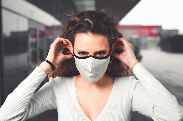 Jeune femme caucasienne portant un masque blanc dans la rue