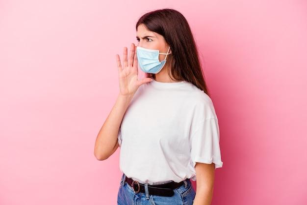 Jeune femme caucasienne portant un masque pour virus isolé sur mur rose criant et tenant la paume près de la bouche ouverte.