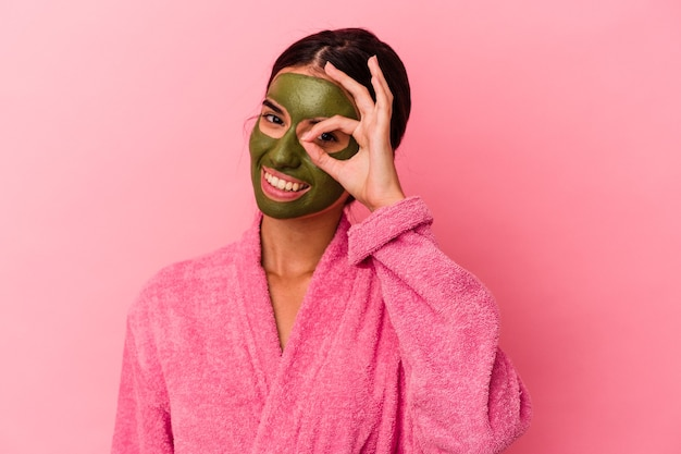 Jeune femme caucasienne portant un peignoir et un masque facial isolé sur fond rose excité en gardant le geste correct sur les yeux.
