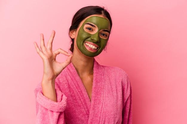 Jeune femme caucasienne portant un peignoir et un masque facial isolé sur fond rose joyeux et confiant montrant un geste correct.