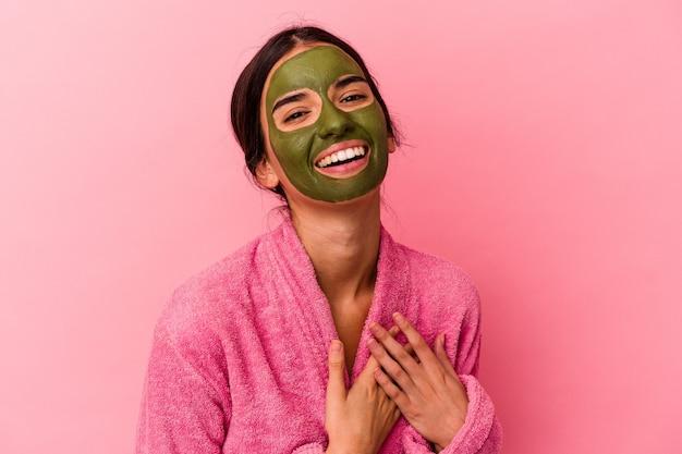 Jeune femme caucasienne portant un peignoir et un masque facial isolé sur fond rose rit fort en gardant la main sur la poitrine.