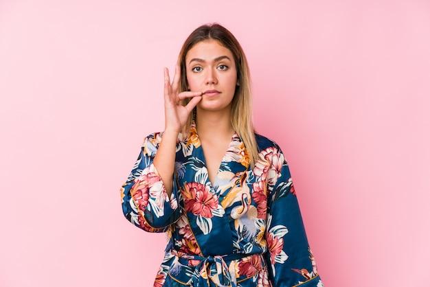 Jeune femme caucasienne portant un pyjama avec les doigts sur les lèvres, gardant un secret.