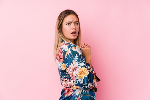 Jeune femme caucasienne portant un pyjama effrayé et effrayé.