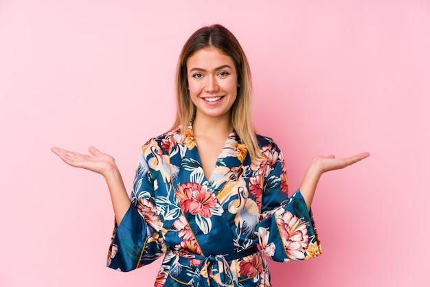 Jeune femme caucasienne portant un pyjama fait l'échelle avec les bras, se sent heureuse et confiante.