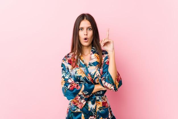 Jeune femme caucasienne portant un pyjama kimono ayant une excellente idée, concept de créativité.