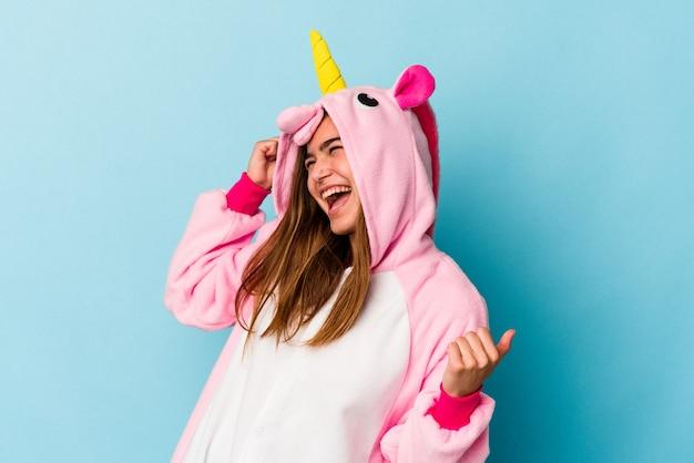 Jeune femme caucasienne portant un pyjama licorne s'amusant isolé sur fond bleu