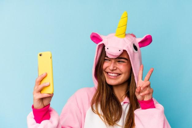 Jeune femme caucasienne portant un pyjama de licorne tenant un téléphone portable isolé sur fond bleu