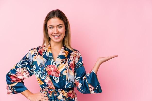 Jeune femme caucasienne portant un pyjama montrant un espace vide sur une paume et tenant une autre main sur la taille.