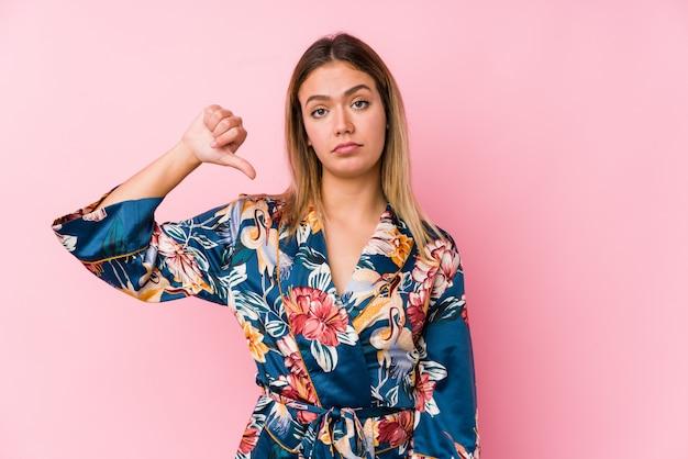 Jeune femme caucasienne portant un pyjama montrant un geste d'aversion, les pouces vers le bas. concept de désaccord.