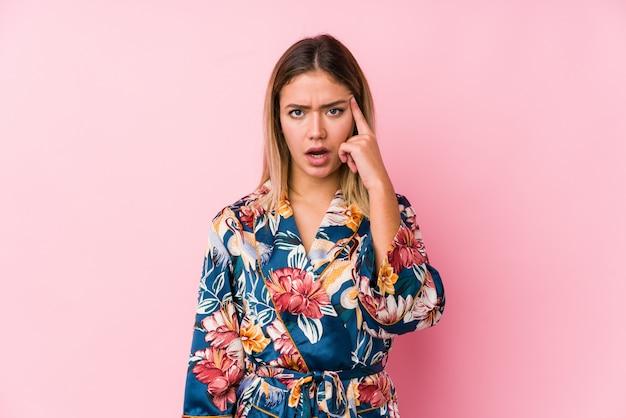 Jeune femme caucasienne portant un pyjama montrant un geste de déception avec l'index.