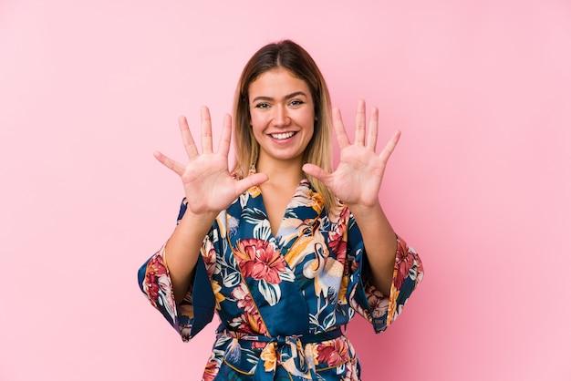 Jeune femme caucasienne portant un pyjama montrant le numéro dix avec les mains.