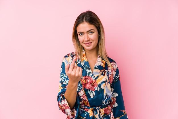 Jeune femme caucasienne portant un pyjama pointant avec le doigt vers vous comme si vous vous invitiez à vous rapprocher.