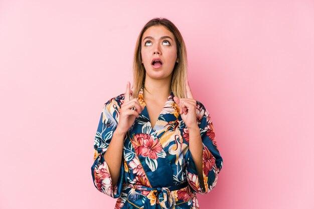 Jeune femme caucasienne portant un pyjama pointant à l'envers avec la bouche ouverte.