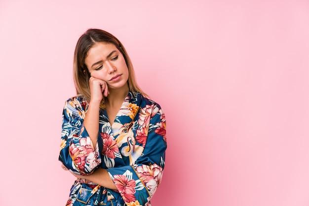 Jeune femme caucasienne portant un pyjama qui se sent triste et songeur, regardant l'espace vide.