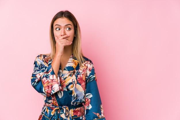 Jeune femme caucasienne portant un pyjama réfléchi à la recherche d'un espace vide couvrant la bouche avec la main.