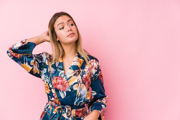 Jeune femme caucasienne portant un pyjama touchant l'arrière de la tête, pensant et faisant un choix.