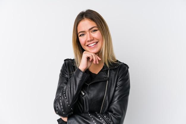 Jeune femme caucasienne portant une veste en cuir noir souriant heureux et confiant, touchant le menton avec la main.