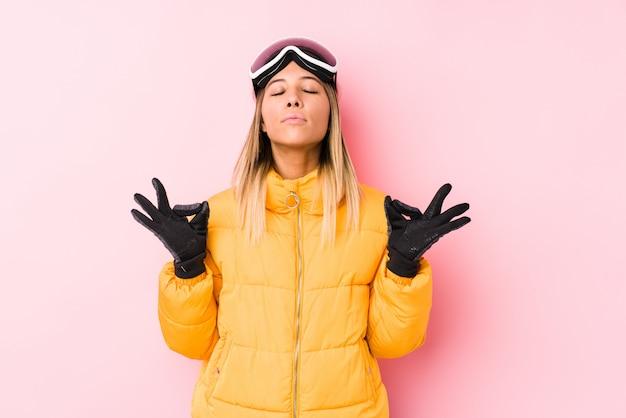 Jeune femme caucasienne portant un vêtement de ski dans un mur rose se détend après une dure journée de travail, elle effectue du yoga.