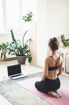 Jeune femme caucasienne portant des vêtements de sport fait du fitness sur le sol avec un ordinateur portable