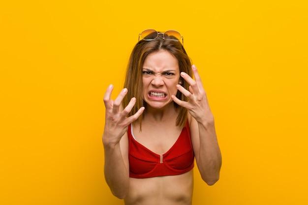 Jeune femme caucasienne, porter des lunettes de soleil et bikini bouleversé crier avec les mains tendues.