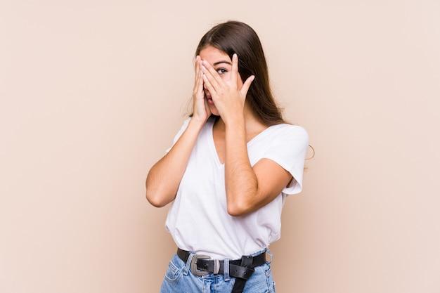 Jeune femme caucasienne posant un clin d'œil isolé entre les doigts effrayé et nerveux.