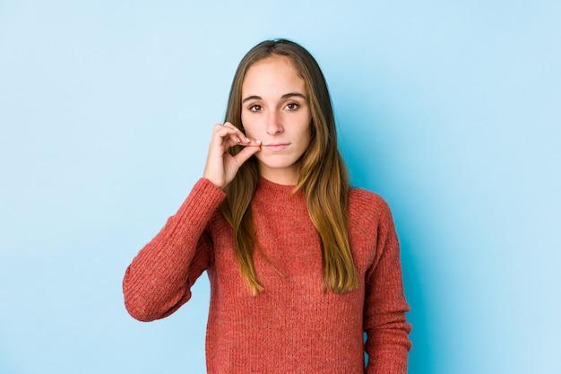 Jeune femme caucasienne posant isolé avec les doigts sur les lèvres en gardant un secret.