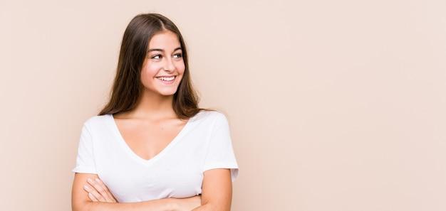 Jeune femme caucasienne posant isolé souriant confiant avec les bras croisés.