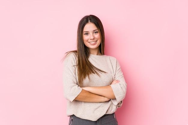 Jeune femme caucasienne posant isolée qui se sent confiant, croisant les bras avec détermination.